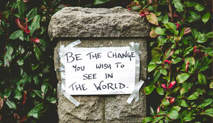 Handwritten sign Be the change you wish to see in the world Ghandi